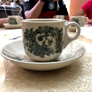 Thick white china cup with the greenish pattern
